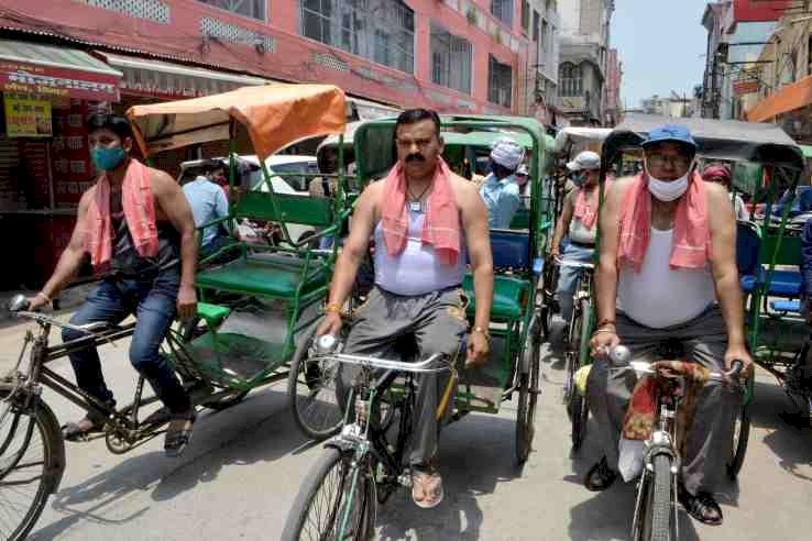 व्यापारियों ने रिक्शा चलाकर किया कोरोना कर्फ्यू विरोध